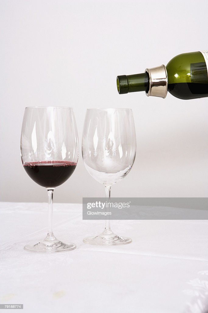 Wine being poured into wine glasses : Stock Photo