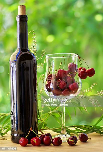 Wine Bottle And Cherries Inside Wineglass