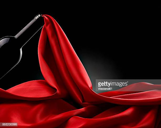 Wine bottle and flowing red silk in front of black background