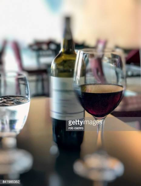 wine bottle and glass - rob castro stock pictures, royalty-free photos & images