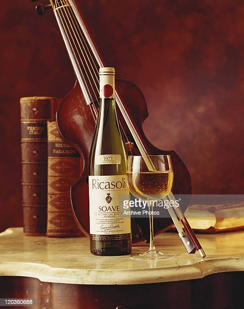 Wine bottle and glass with violin in background, close-up