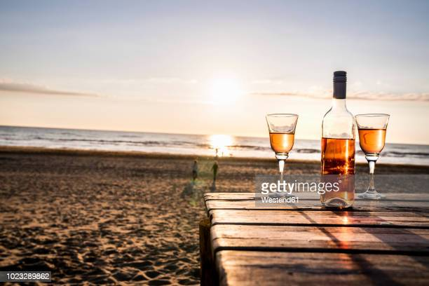Wine bottle and glasses on boardwalk on the beach at sunset