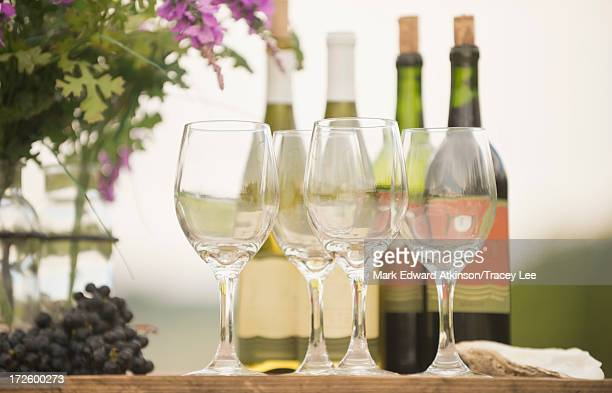 wine bottle, grapes and glasses on table outdoors - chardonnay grape - fotografias e filmes do acervo