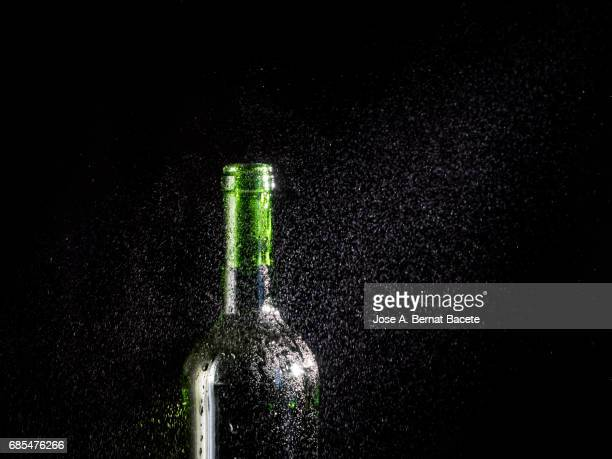 Wine bottle of beer with the frosted glass with drops of water and a steam cloud frozen on a black bottom
