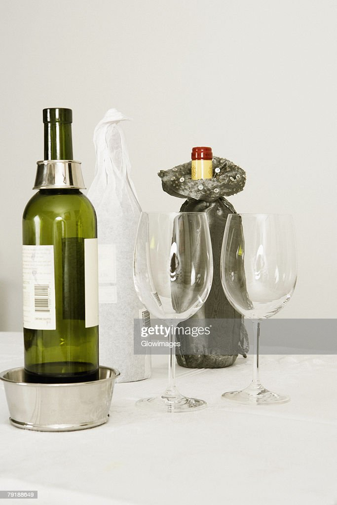Wine bottles and two wine glasses on a dining table : Foto de stock