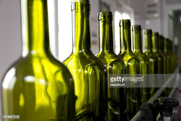 Wine bottles colored green on an assembly line