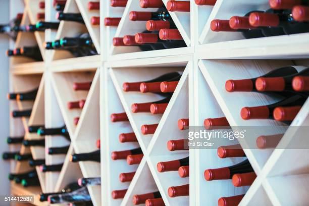 Wine bottles in rack on wall