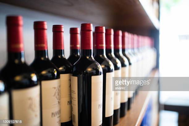 wine bottles on shelf at a winery - wine bottle stock pictures, royalty-free photos & images