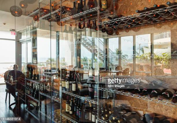 wine bottles on shelves in restaurant - southeast stock pictures, royalty-free photos & images