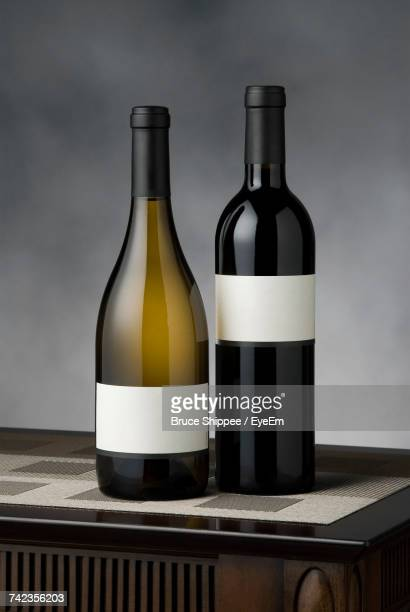 Wine Bottles On Table Against Gray Wall