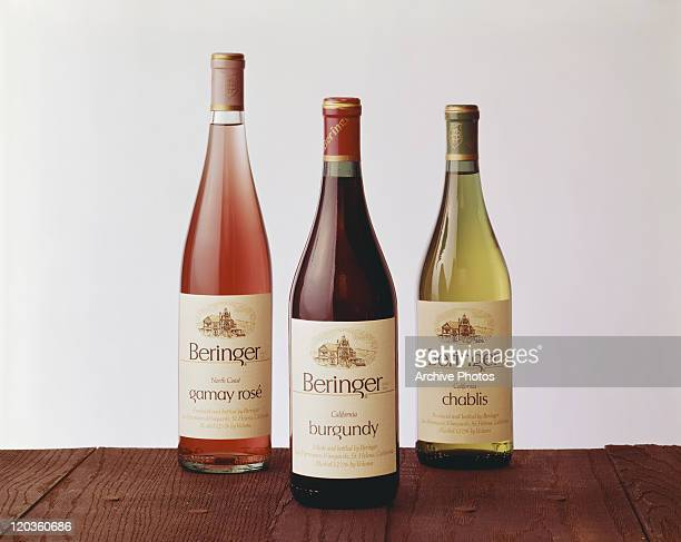Wine bottles on table against white background, close-up