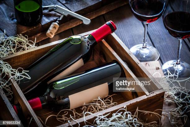 Wine bottles packed in a wooden box shot rustic wooden table