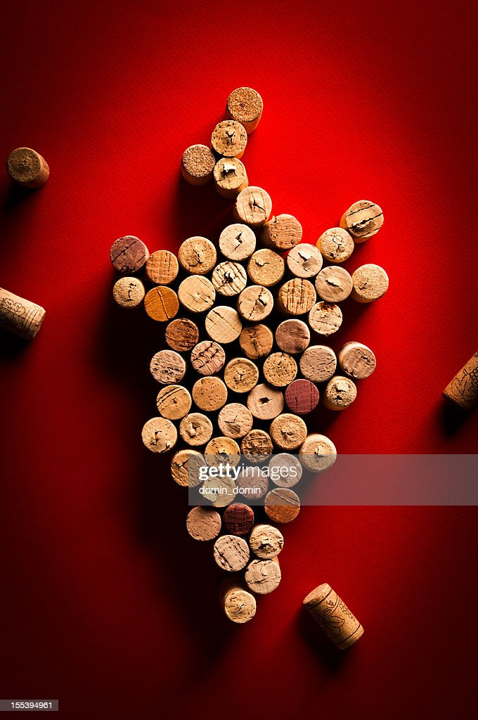 Wine corks arranged in a grapes shape on red background : Stock Photo