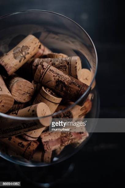 wine corks with brand-names and logos in  the glass. - cork stopper stock photos and pictures