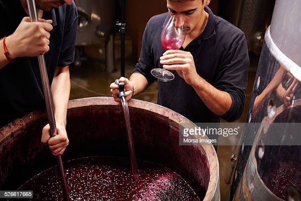 Wine expert tastes the wine before closing barrels