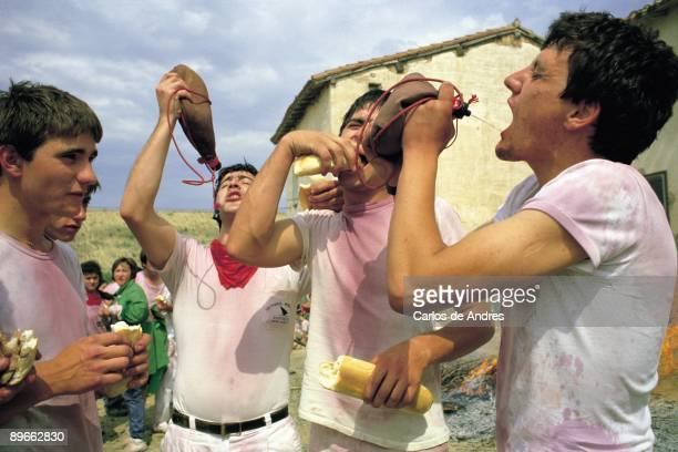 Wine festivity, Haro, La Rioja Four men eat bread and drink wine of a leather bottle during the festivity of the wine in the town of Haro