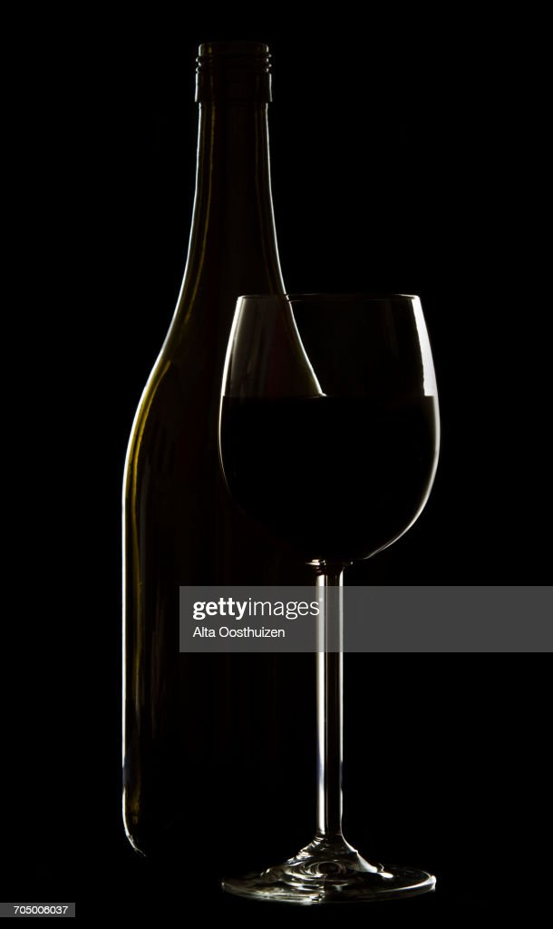 Wine glass and bottle on black background rim lighting  Stock Photo & Wine Glass And Bottle On Black Background Rim Lighting Stock Photo ...