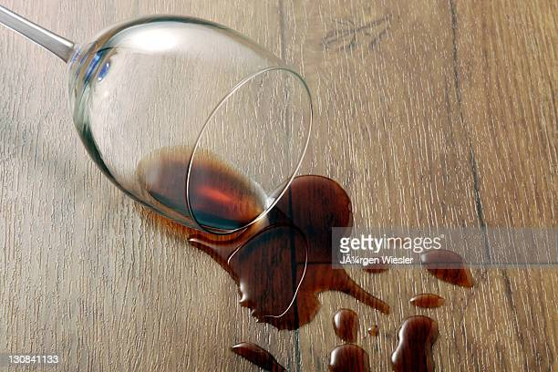 wine glass and spilled red wine on a durable vinyl flooring with wood effect - wood effect stock photos and pictures