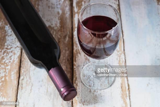 wine glass and wine bottle on old wood background - uvas cabernet sauvignon - fotografias e filmes do acervo