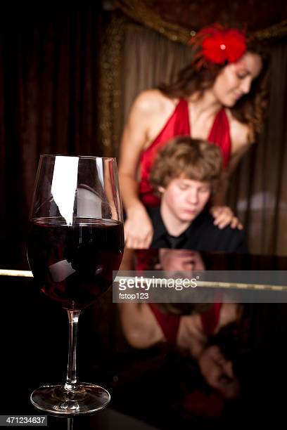 wine glass on piano with pianist and soloist in background - keyboard player stock photos and pictures