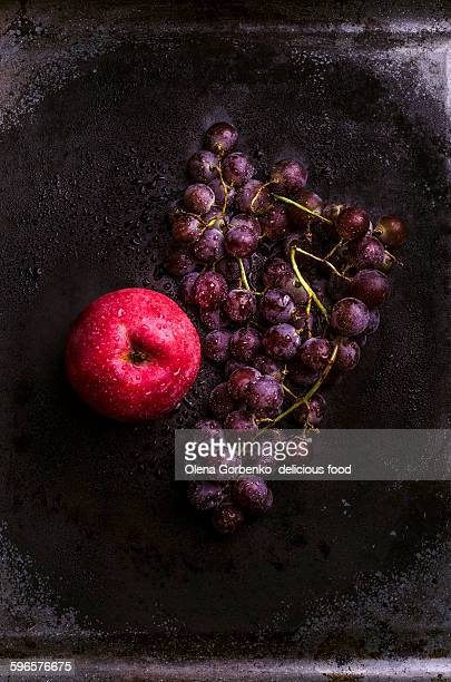 Wine grapes and red apple on rustic background