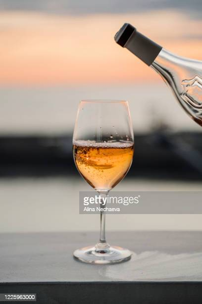wine is pouring from the bottle into the glass with sunset sea view on the background - alina stock pictures, royalty-free photos & images