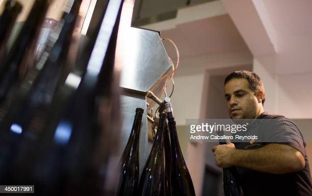 Wine maker Tasos Chrystou bottles red wine at the Hadjiantonas Winery on November 16 2013 in Parekklisia Cyprus With wine production averaging...