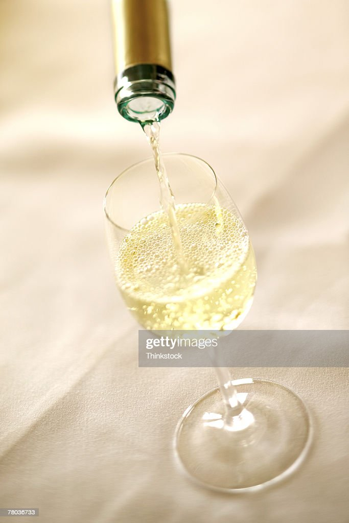 Wine pouring from bottle into glass : Stock Photo