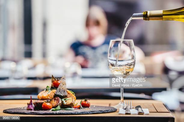 wine pouring in wineglass by food on table at restaurant - 背景に人 ストックフォトと画像