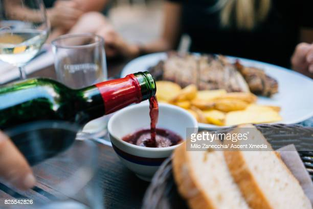 Wine pouring into small cup at restaurant,