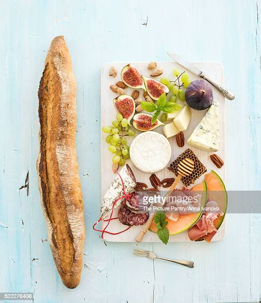 Wine snack set. Baguette, figs, grapes, nuts, cheese variety, meat appetizers, herbs on light blue b