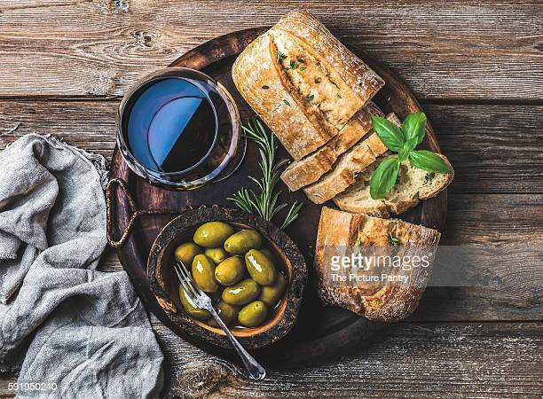 Wine snack set. Glass of red wine, green mediterranean olives, freshly baked ciabatta bread in dark wooden plate over rustic wooden background