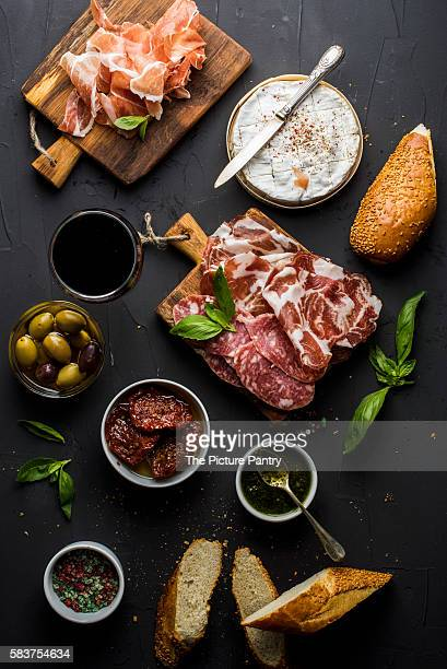 Wine snack set with empty wooden board in center. Glass of red, meat selection, mediterranean olives, sun-dried tomatoes, baguette slices, camembert cheese and spices on black background,