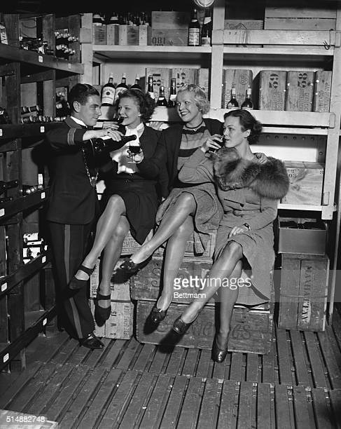 Wine steward Joel Goodman shares a drink in the wine cellar aboard the cruise ship Manhattan with showgirls Helen Day Lovee Babalis and Evelyn Page...
