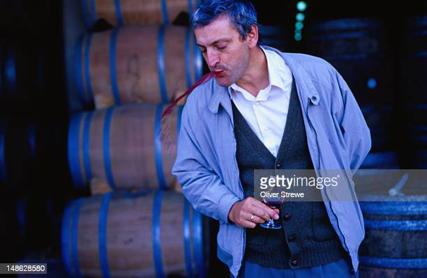 Wine taster from Bodegar ( winery ) de Sarria spitting out red wine - Puente de la Reina, Navarra