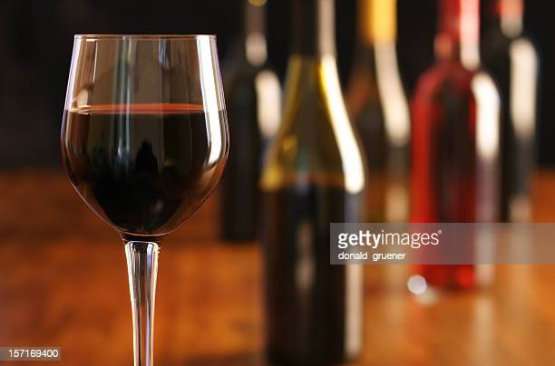 Wine Tasting with glass of red wine and multiple bottles