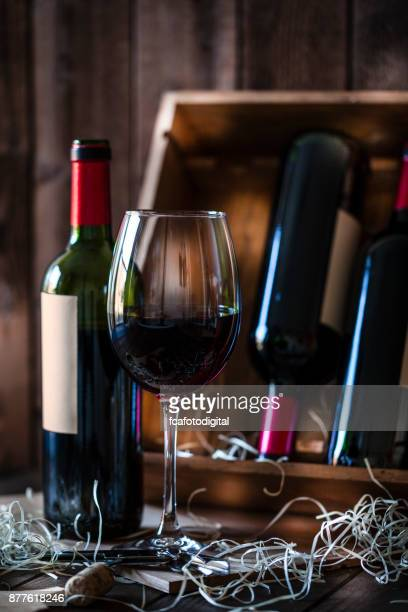 Wineglas and red wine bottle shot rustic wooden table