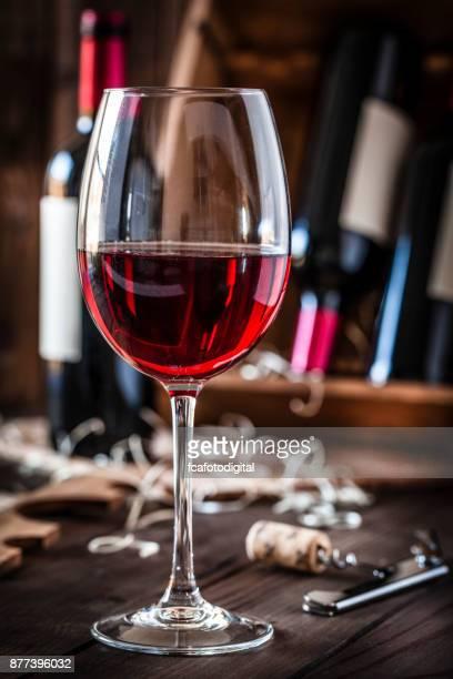 Wineglas con mesa madera rústico tiro vino rojo