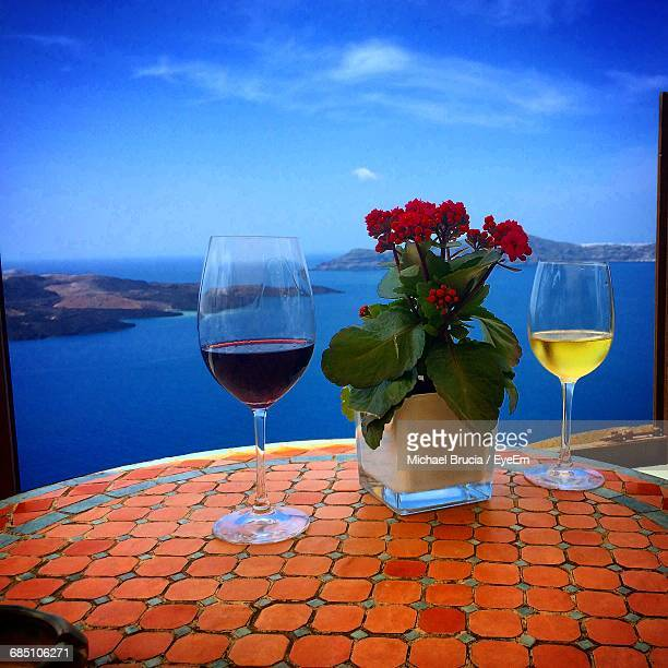 Wineglasses And Flower Pot On Table At Restaurant Against Sea