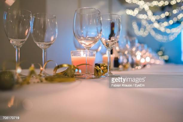 wineglasses and tea light candles on table in party - christmas still life stock pictures, royalty-free photos & images