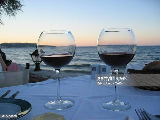 Wineglasses On Table At Beach During Sunset