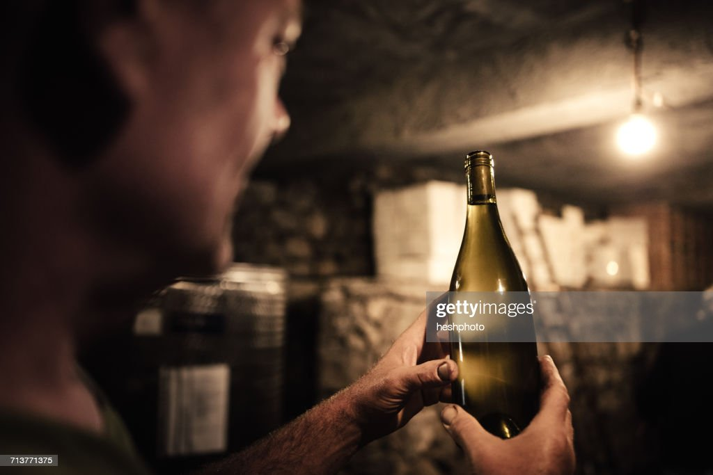 Winemaker gazing at wine bottle in cellar : Stock Photo