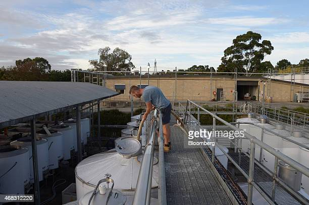 Winemaker Keith Spencer uses a hose to wet the top of a fermenting vat with wine from the bottom of the same vat at the Rob Dolan Co winery in the...