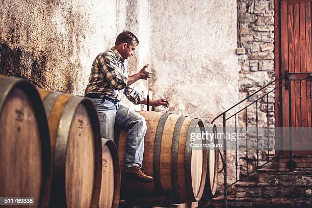 Winemaker Pouring Red Wine into Glass with Pipette