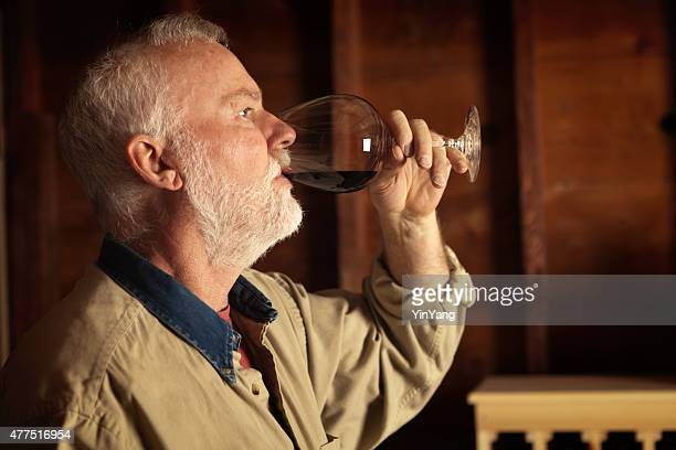 Winemaker Studying and Tasting Wine in Cellar Horizontal