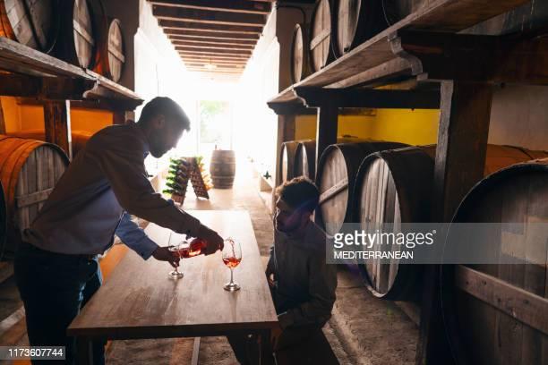 ワイナリーセラーでワインテイスティングをするワインメーカー - 地下貯蔵室 ストックフォトと画像
