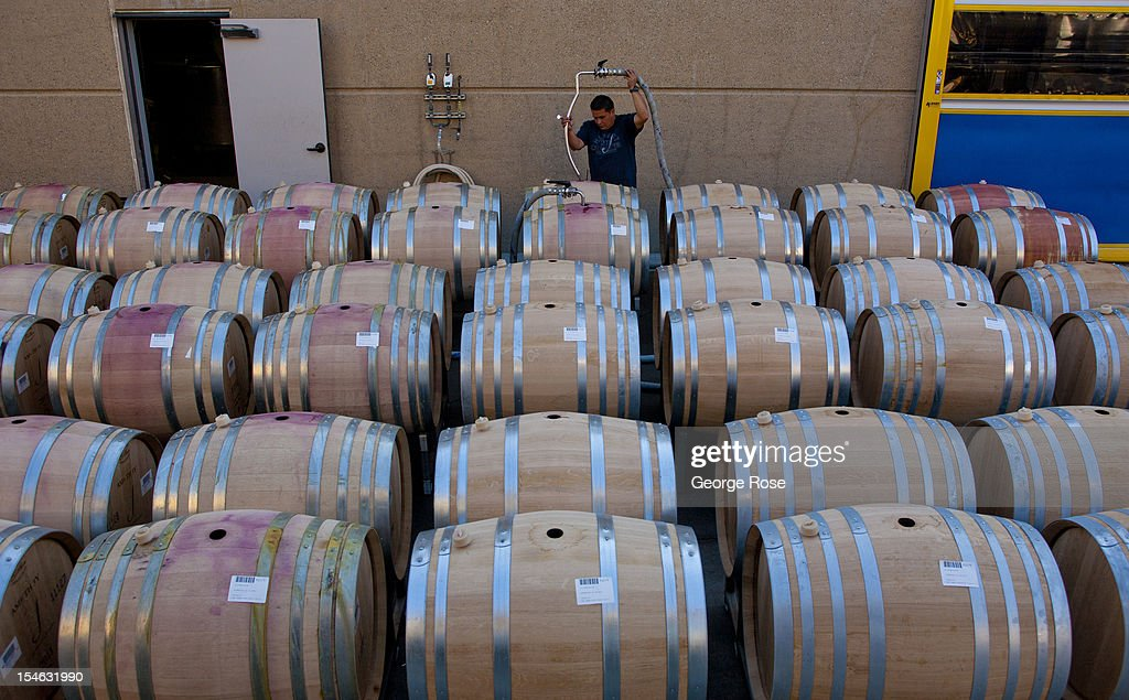 A winery cellar worker at J Vineyards Winery pumps fermented pinot noir juice into new French & Panorama Of Wine Cellar Stock Photos and Pictures | Getty Images