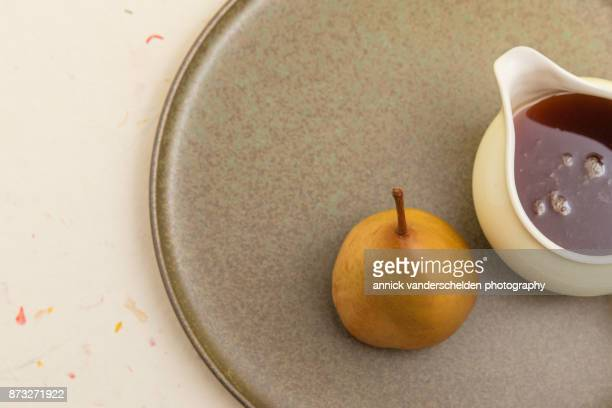 Wine-steamed Durondeau pear and sauce served on platter.