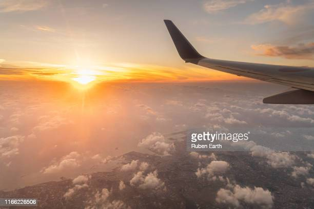 wing and sunset over okinawa island - aircraft wing stock pictures, royalty-free photos & images