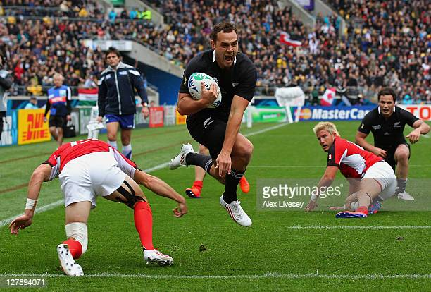 Wing Israel Dagg of the All Blacks leaps through the challenge from Matt Evans of Canada to score his team's third try during the IRB Rugby World Cup...